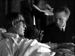 A dying Professor Morlant (Boris Karloff) gives final instructions to his butler (Ernest Thesinger) in The Ghoul